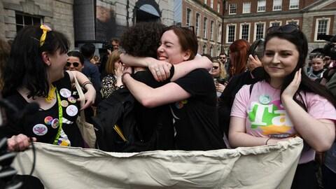 Deux femmes, l'une frisée, l'autre non, s'enlacent. Celle de gauche sourit, entourée par la foule.