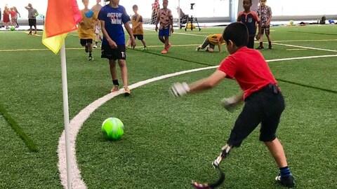 Un jeune garçon tente de faire un arrêt du ballon sur un terrain de soccer.