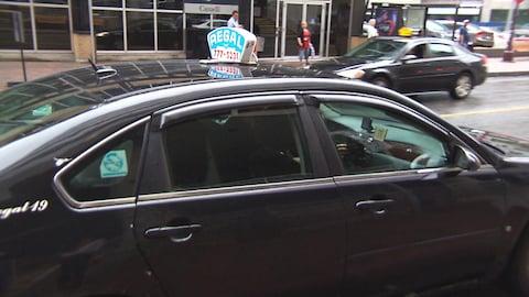 Un taxi noir stationné, de la compagnie Regal