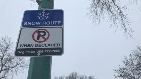 Un panneau bleu avec un flocon de neige accompagne un signe « interdit de stationner » sur une rue enneigée.