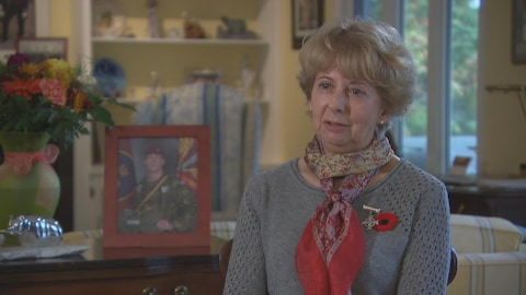 Une femme portant un coquelicot et une épinglette qui représente une croix d'argent est interviewée.