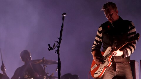 Le chanteur du groupe Queens of the Stone Age, Josh Homme, sur scène avec sa guitare lors d'un spectacle à Rio de Janeiro, en 2014.
