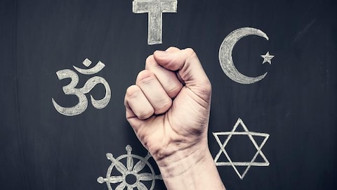 Un poing devant des signes de diverses religions