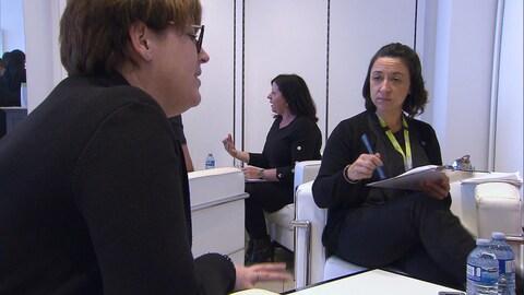 Deux femmes discutent, assises sur des fauteuils blancs. En arrière-plan, une troisième aux cheveux noirs parle en s'aidant de ses mains.