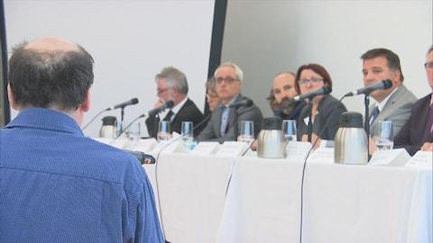 Un homme de dos pose une question à des représentants des gouvernements du Québec et du Canada.