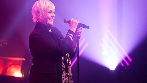 La chanteuse country Renée Martel devant un micro.
