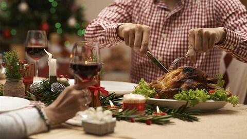 Un homme coupe une dinde autour d'une table décorée pour Noël.