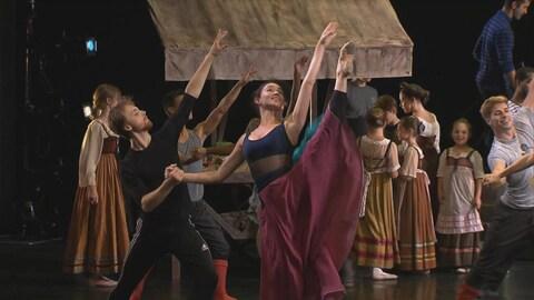 Image captée lors d'une répétition d'un spectacle qui doit être présenté au Festival des arts de Saint-Sauveur. On y voit de nombreux danseurs qui s'exécutent sur scène.