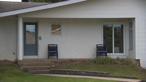 Une fenêtre de la maison est bouchée avec du contreplaqué