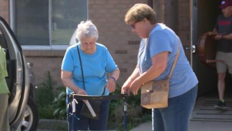 Une personne âgée marchant aidée par une employée