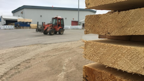 Des planches de bois sont empilées à l'extérieur de l'usine.