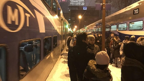Les usagers font la file sur un terre-plein, entre deux chemins de fer.