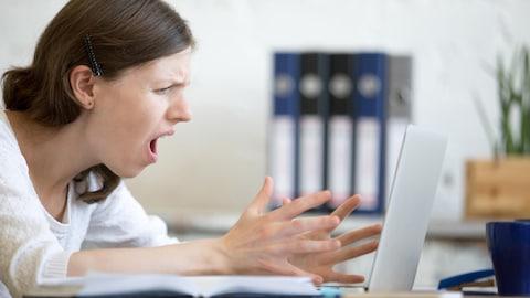 Une jeune femme assise devant un ordinateur portable affiche une expression de dégoût et de frustration.