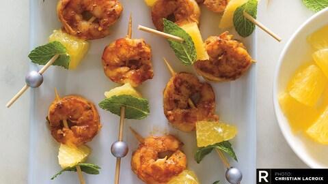 Des brochettes de crevettes à l'orange dans une assiette rectangulaire.