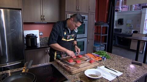 Le chef autochtone Rich Francis prépare un plat de saumon dans sa cuisine.