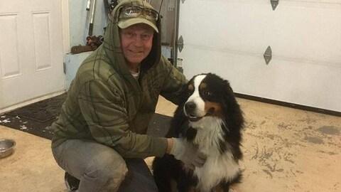 Un homme est agenouillé et tient un chien de race bouvier bernois.