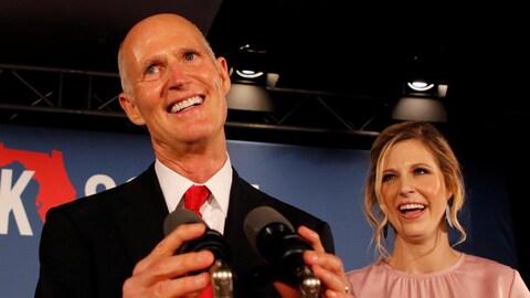 Rick Scott, chauve et rasé de près, arbore un sourire. Il est vêtu d'un costume sombre réhaussé d'une cravate rouge. Sa fille a un haut rose et sourit franchement.