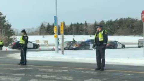 Deux policiers qui arrêtent la circulation.