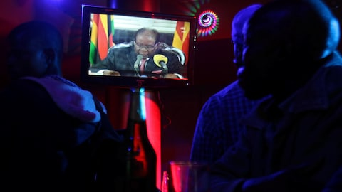 Les clients d'un bar regardent Robert Mugabe sur un écran de télévision.