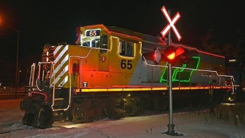 Une locomotive de train décorée avec des lumières et une couronne de Noël circule sur le chemin de fer Roberval-Saguenay.