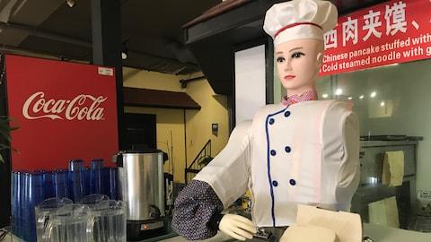 Le robot est habillé en chef cuisinier et est utilisé dans le restaurant Number 1 Noodle House à Saskatoon qui sert des mets chinois.