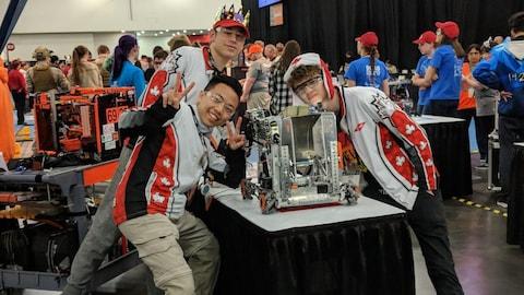 Trois élèves de l'équipe Helios 5009 posent devant leur robot, posé sur une table, sur le site du championnat.