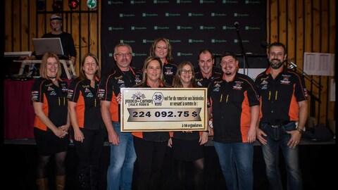 Des membres d'un comité organisateur tiennent un gros chèque de 224 092,75 $.