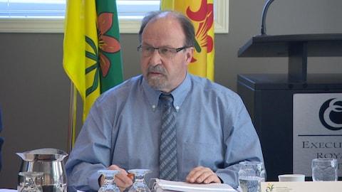 Le président de l'ACF, Roger Gauthier, préside l'Assemblée des députés communautaires, assis devant les drapeaux de la Saskatchewan et fransaskois.