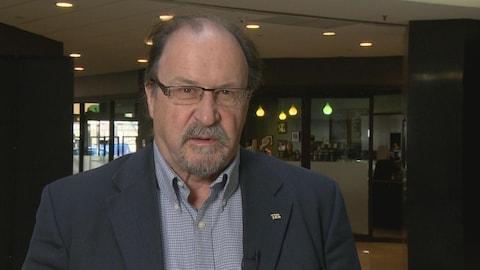 Roger Gauthier se trouve dans un corridor assez sombre. Il porte une chemise et un veston bleus.