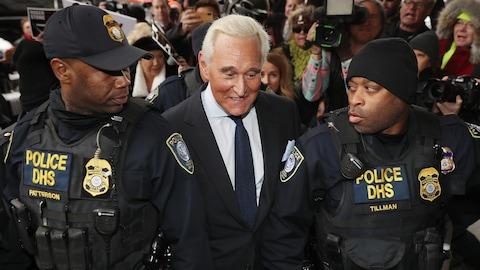 Roger Stone, en complet, est escorté par deux agents armés du département de la Sécurité intérieure.