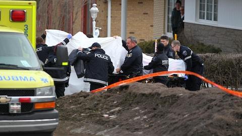 Le corps de Rosalie Gagnon sur une civière. Plusieurs policiers tente de cacher la civière à l'aide d'une couverture.