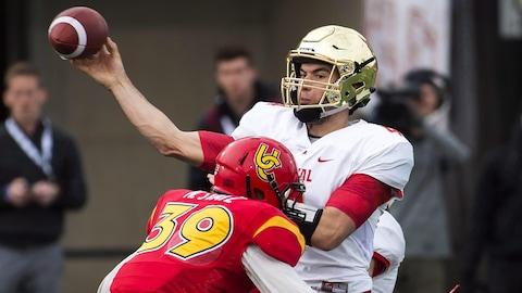 Le quart-arrière du Rouge et Or Hugo Richard lance le ballon sous la pression d'un joueur des Dinos de l'Université de Calgary