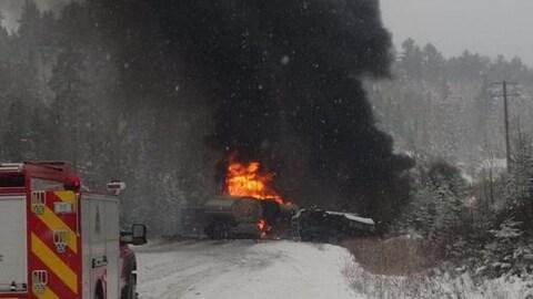 Camion enflammé sur une route enneigée.