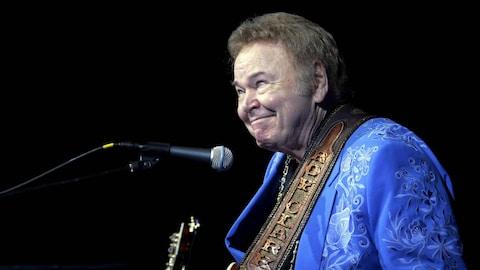 Roy Clark sourit sur scène avec sa guitare.