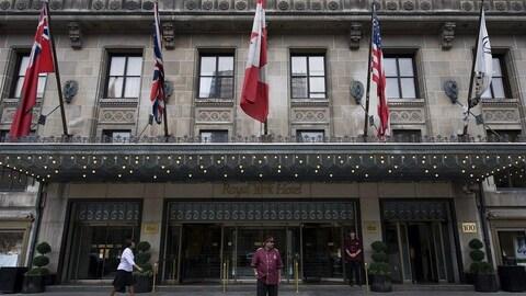 Des employés se tiennent devant l'hôtel Royal York de Toronto.