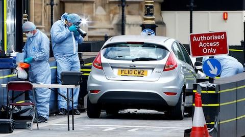 Des enquêteurs inspectant une voiture.