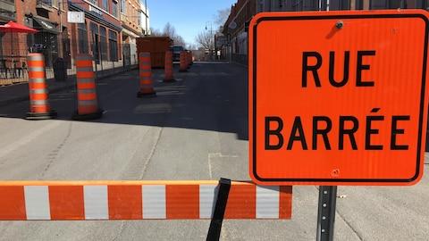 Une barrière bloque l'accès à une rue, devant laquelle il y a une pancarte orange avec la mention rue barrée.