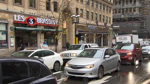 Des voitures sur la rue Sainte-Catherine devant des commerces.