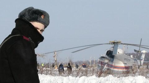 Un militaire russe déployé sur le site de l'accident jette un coup derrière lui. À sa droite, on peut voir un hélicoptère posé au sol. Des enquêteurs sont au travail tout près.