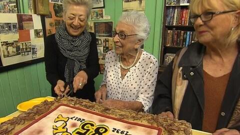 La fondatrice du célébre restaurant entourée de deux femmes devant un gâteau.