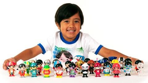 Une photo montrant Ryan derrière une trentaine de figurines colorées posées sur une table.