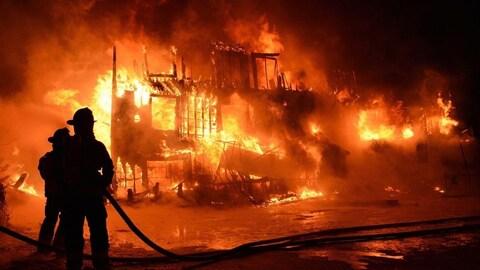 Deux pompiers combattent l'incendie de la Résidence du Havre de L'Isle-Verte, près de Rivière-du-Loup, qui a fait 32 morts le 23 janvier 2014.