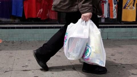 Un passant portant des épiceries dans des sacs jetables