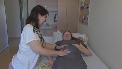 Une sage-femme examine une femme enceinte.