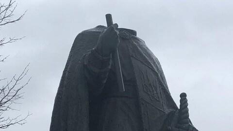 Une statue sans tête avec un ciel nuageux.