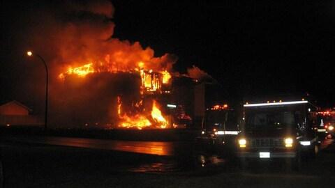 un immeuble en feu et un camion d'incendie.