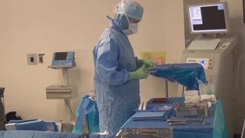 Une personne habillée d'une combinaison sanitaire s'affaire dans une salle d'opération.