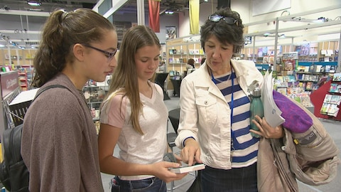 Gilberte Godin en compagnie de deux élèves au salon du livre