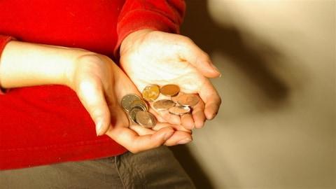 Une personne tient quelques cents dans ses mains