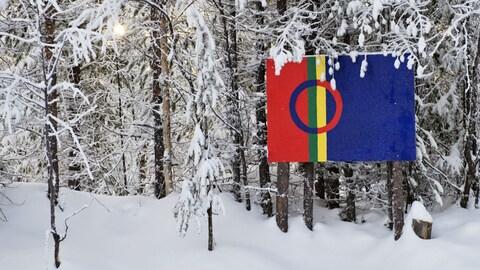 Un drapeau accroché à des arbres enneigés.
